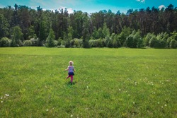 little girl run and play in summer nature,