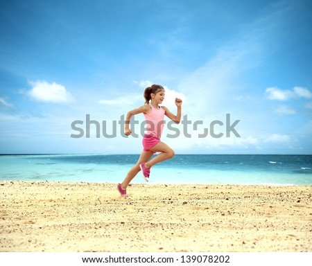 Little girl running along ocean