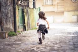 Little girl running down a cobblestone alley