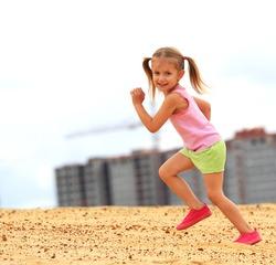 Little girl running in sand