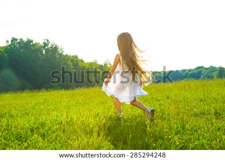 Stock Photo Little girl running on green grass. Beautiful warm summer evening.