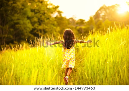 Stock Photo Little girl running on meadow with sunset