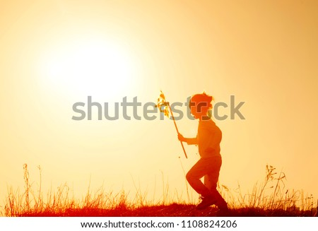 Little girl running on the meadow at sunset with windmill in her hands. Silhouette of child girl holding wind toy