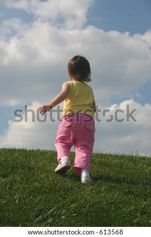 Little girl running up a hill. - stock photo