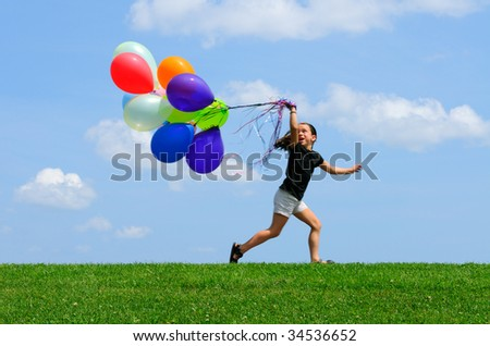 Little girl running with balloons on top of the hill. Green grass, blue sky background.