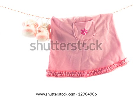 Little girl's clothes and slippers hanging on a rope. Copy space