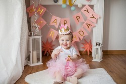 Little girl's first birthday party. Portrait of a girl in a festive dress with an anchor for her first birthday. Baby.