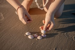 Little girl's hands creating a heart from seashells on the ocean sandy beach. Summer leisure, love concept.