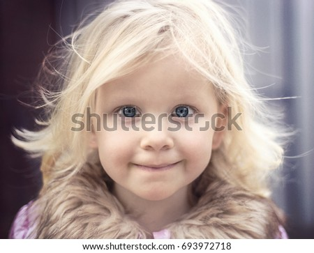 little girl's smiling face. Blond girl with blue eyes close up