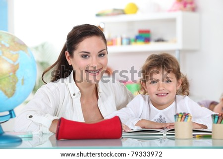 Little girl sat with teacher in class room