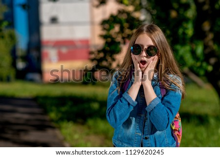 Little girl schoolgirl teenager. Summer nature. In jeans clothes and sunglasses. The concept surprise, fear, surprise, gift, surprise. Emotions happiness joy and pleasure. Free space for text. #1129620245