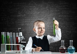 Little girl scientist examining test tube with chemical reagent. Research and education in school. Chemical laboratory with microscope and glass flasks. Schoolgirl making experiment in chemistry class