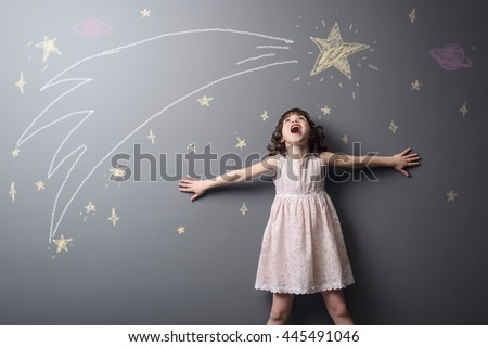 Little girl screams from pleasure to see a shooting star, the grace of the space and big planet depicted with chalk on the grey wall in studio. True emotion of happiness.