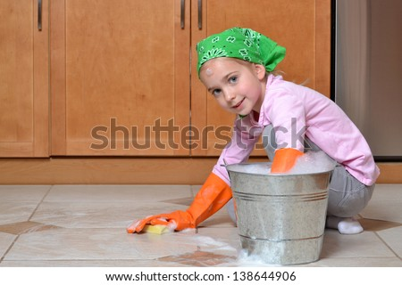 little girl scrubbing tile floor spring cleaning