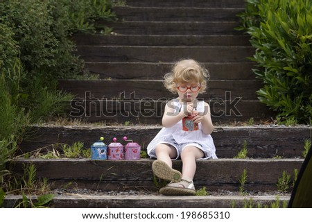 little girl seated on old wooden stairs with musical boxes