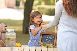 Little girl selling lemonade at counter in park