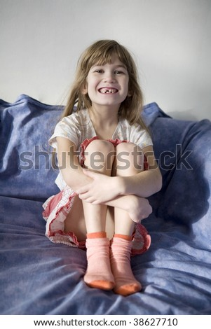 Little girl seven years old sitting on bed