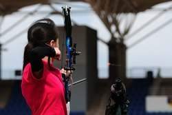 Little girl shoot at outdoor archery competition