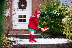 Little girl shoveling snow on home drive way. Beautiful house decorated for Christmas. Child with shovel playing outdoors in Xmas season. Family removing snow during blizzard. Kids play outside.