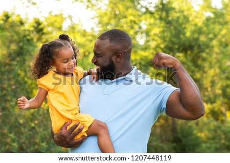 Little girl showing her mussels to her dad.