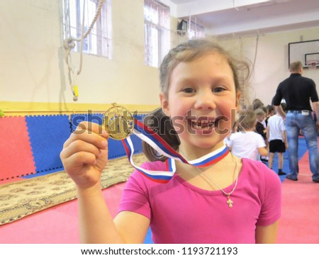 little girl shows gold medal for winning a gymnastics competition in the gym #1193721193