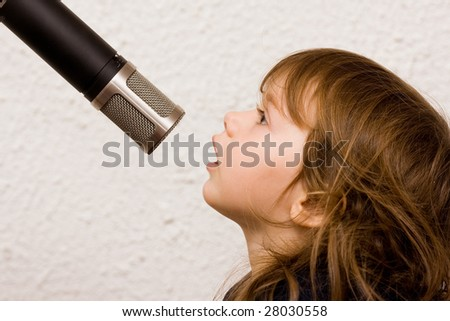 Little girl singing a song in a microphone