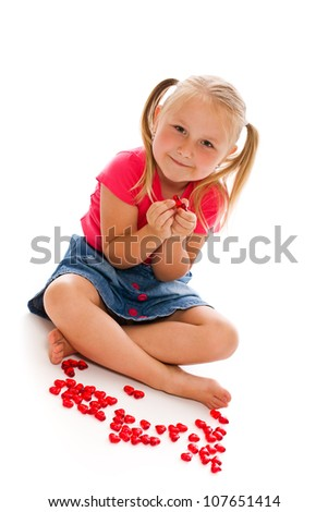 little girl sit on white floor with red hearts
