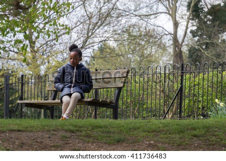 Little girl sits alone on a park bench
