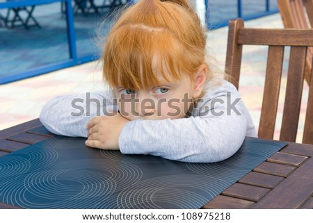 little girl sits at a table