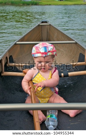Little girl sits in the canoe holding the paddle getting ready for a ride