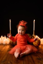 Little girl sits on a background of Jack pumpkins and candles on a black background. The baby looks into the frame with her eyes screwed up.