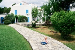 Little girl sits on a cobbled path in the garden in front of the house