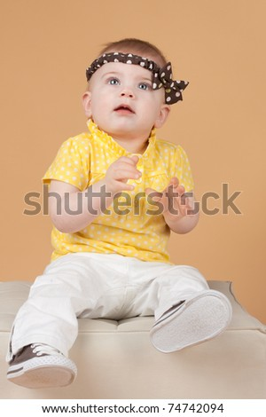 Little girl sits on a white ottoman, a studio portrait
