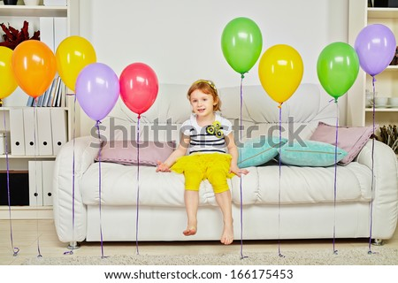 Little girl sits on big sofa in room with carpet on floor and birthday air balloons