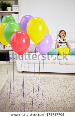 Little girl sits on big sofa in room with light carpet on floor and birthday air balloons