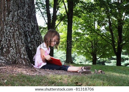 Little girl sits outdoors under a large oak tree and reads a book.