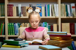little girl sits with books at table in library,child in bookstore, surrounded by colorful books for school