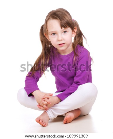 little girl sitting and looking seriously as if thing of something or intending to do something