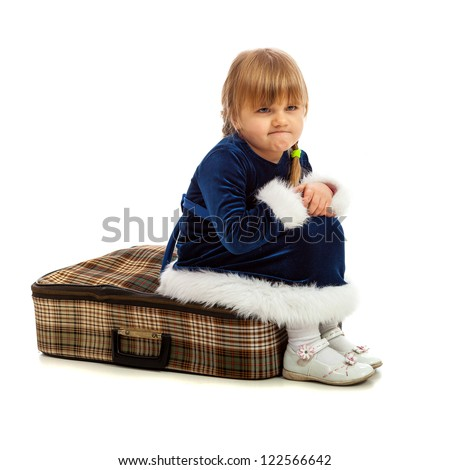 Little girl sitting angry on big travel suitcase isolated on white