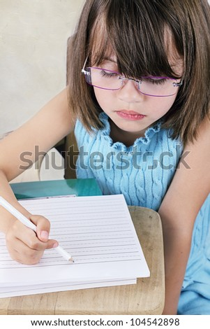 Little girl sitting at a school desk writing.
