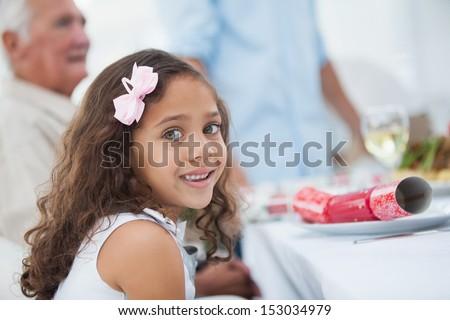 Little girl sitting at table for christmas dinner and looking at camera