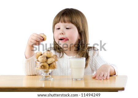 Little girl sitting at the wooden table having Breakfast isolated on white