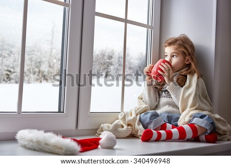 little girl sitting by the window with a cup of hot drink and looking at the winter forest #340496948