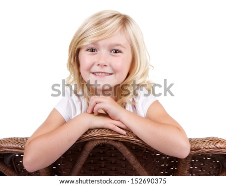 little girl sitting in chair with a happy look on her face, isolated on white background
