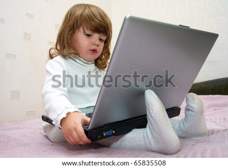 Little girl sitting in front of the monitor laptop at home on the couch.