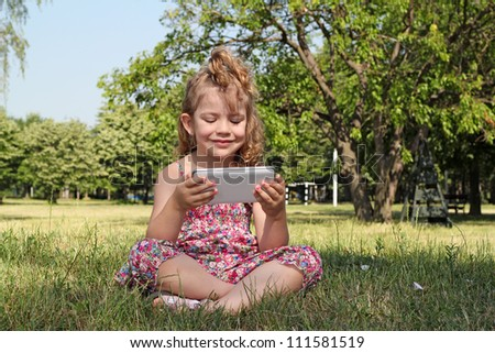 little girl sitting in park and play with tablet pc