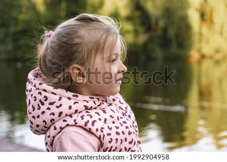 Little girl sitting in park near the lake