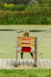 Little girl sitting in the giant wooden chair on the lake bank