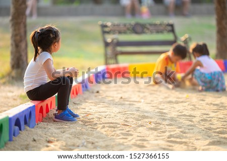 Little girl sitting lonely watching friends play at the playground.The feeling was overlooked by other people.Concept child shy.