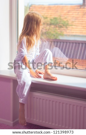 Little girl sitting near the window and looking to outdoors